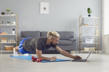 Man doing low-impact HIIT workout video in his living room on his computer