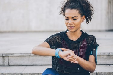 woman checking her smart watch to see why heart rate is high after a workout