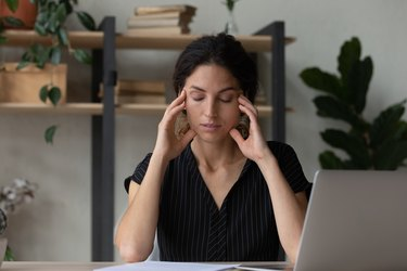 Tired young woman overwhelmed with computer work