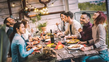 young adults dining and drinking outside at picnic table