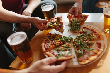 A group of people eating pizza and drinking beer, as an example of foods that irritate hiatal hernia