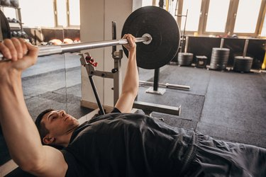 side view of a young fit man doing a barbell bench press in a the gym, in need of bench press alternatives