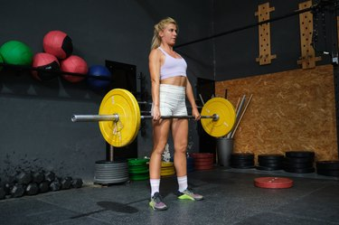 Young blonde woman doing a deadlift exercise in a crossfit gym, enjoying deadlift benefits