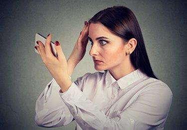 Upset woman surprised she is losing hair has receding hairline. Human emotion.