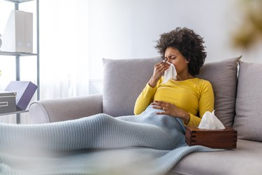 Woman sneezing in a tissue in the living room.