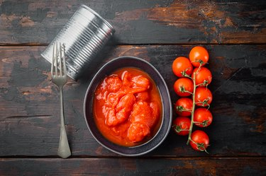 Peeled canned tomatoes and Fresh Tomatoes, on old dark  wooden table background, top view flat lay