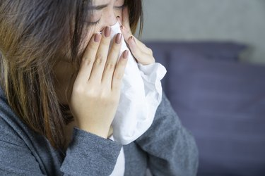 close up of person using a tissue to blow nose and check snot to see if something is wrong with their health