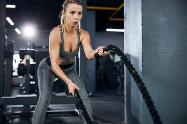 athlete holding the ends of two battle ropes exercising with diverticulitis
