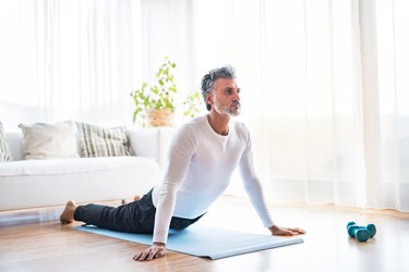 mature man doing exercise for back pain at home on mat in living room