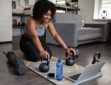 Woman preparing to do an upper body kettlebell workout with her laptop