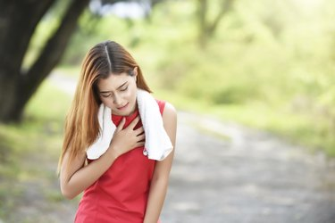 Beautiful Young Woman With Chest Pain Standing Against Blurred Background