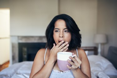 A woman drinking coffee and yawning as a symptom of too much caffeine