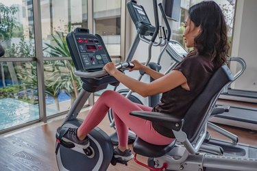 woman using a recumbent best stationary bike for low back pain in a gym
