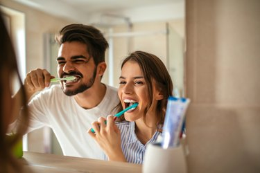 couple brushing their teeth in the bathroom mirror