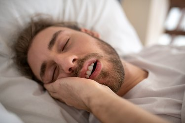 Young man in bed and drooling in his sleep