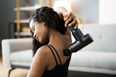 woman using a massage gun on her back and shoulders sitting on the floor at home
