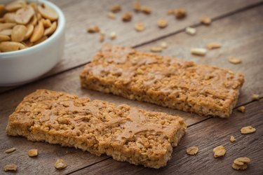 Granola bars on wooden table and peanuts