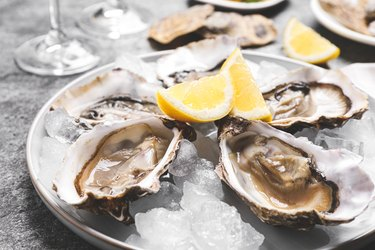 aspartic acid-rich fresh oysters with lemon and ice on grey table