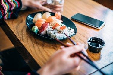 Crop woman eating sushi