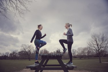 Full length side view of women doing step-ups on picnic bench