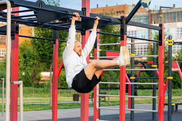 A man performs a leg raise on the bar in the morning on the sports field.