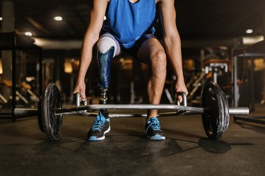 strong man with prosthetic leg doing a hex bar deadlift in the gym