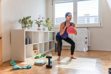 woman doing a goblet squat with a pink kettlebell in her living room