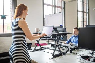 Businesswoman working at ergonomic standing desk