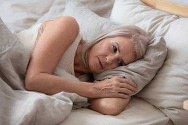 An older woman laying in bed trying to sleep