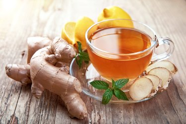 Cup of fresh ginger tea with lemon and mint next to ginger root on a wooden table.