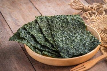 Crispy dried beta-glucan-rich seaweed on a wooden bowl.
