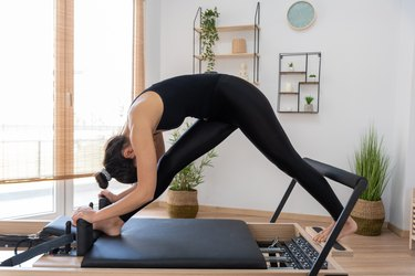 young caucasian woman stretching on and enjoying the benefits of a Pilates reformer