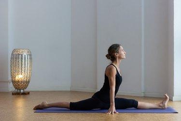 woman doing a split on a purple yoga mat