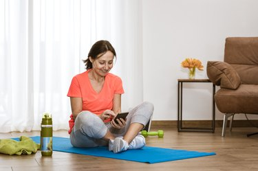 mature woman in orange shirt working out with phone on a blue yoga mat