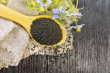 Seeds of black cumin in spoon on board top