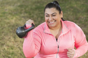 hispanic plus-sized athlete wearing pink, holding a kettlebell in the rack position