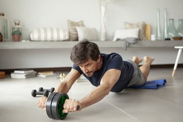 man exercising in living room with an ab roller
