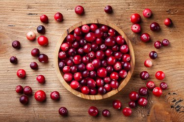 Fresh raw cranberry in wooden bowl on rustic table top view.