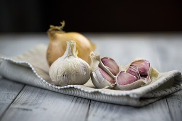 Organic garlic and onion on wooden background, as a natural remedy for bug bite relief