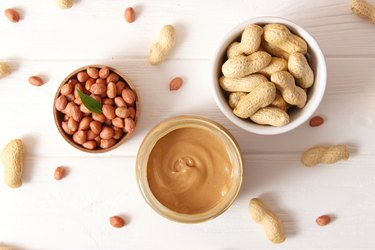 creamy peanut butter and peanuts, one of the most common food allergens, on wooden background top view