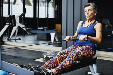 Senior woman working out on rowing machine at outdoor gym
