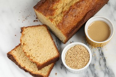 sesame seeds in bowl on table with tahini and bread