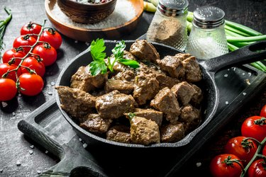 copper-rich fried liver with spices and cherry tomatoes on a cutting Board.