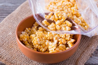 Frozen sweet corn in a bowl on a wooden table