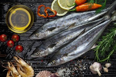 mercury-rich raw mackerel on table with oil and vegetables