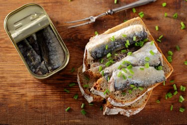 Toast with purine-rich sardines in canned oil on a wooden board