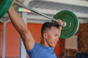 Indonesian Weightlifting Athlete Lifting Heavy Barbell Above His Head