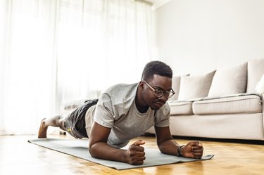 Adult male workout in his living room on yoga mat exercising plank position