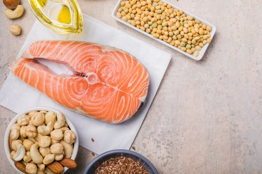 Omega 3 food sources and omega 6 on concrete background, top view copy space. Foods high in fatty acids including vegetables, seafood, nut and seeds