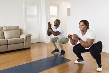 mature black couple doing body-weight squats for a low-impact fat-burning workout